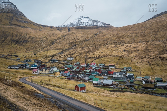 Fantastic view of small settlement and countryside road located in valley near hills on cloudy day on Faroe Islands