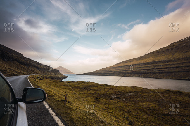 Wing mirror of modern car riding on asphalt road near calm water and wonderful hills on cloudy morning on Faroe Islands