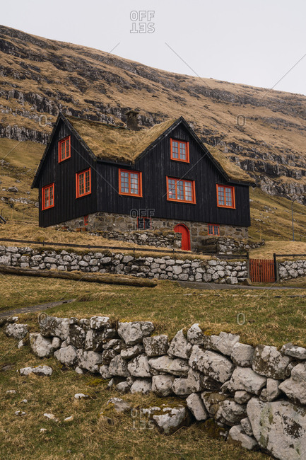 Beautiful cottage with black walls located near rough cliff slope in majestic countryside of Faroe Islands