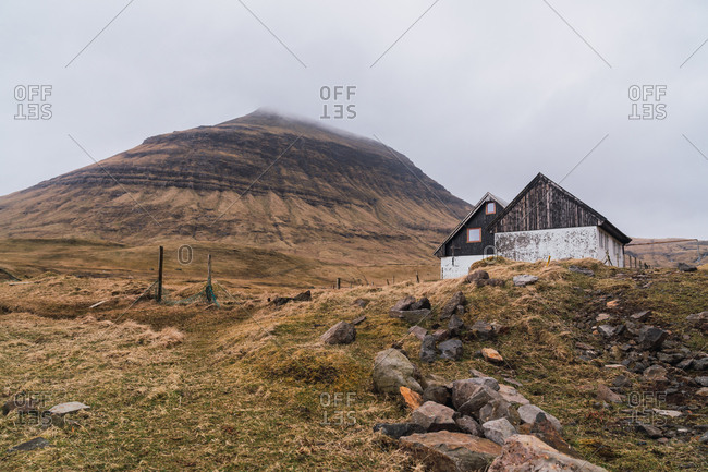 Two shabby lumber shacks located near hill against cloudy gray sky in countryside of Faroe Islands