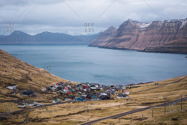 Majestic view of small village amidst hills on coast of amazing tranquil sea on cloudy day on Faroe Islands