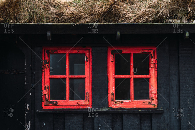 Windows with shabby red frames on black wall of countryside house with hay roof