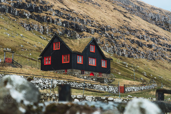 Beautiful black cottage with red windows located on slope of grassy hill on Faroe Islands