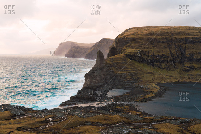 Water of majestic sea rolling near beautiful rocky cliffs during sunrise on Faroe Islands