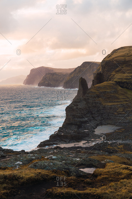 Picturesque view of cloudy sunrise sky over waving blue sea and rough cliffs on Faroe Islands
