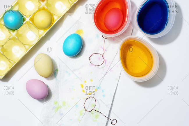 Eggs dyed pink, yellow and blue on a paper towel with cups of dye on a white background.
