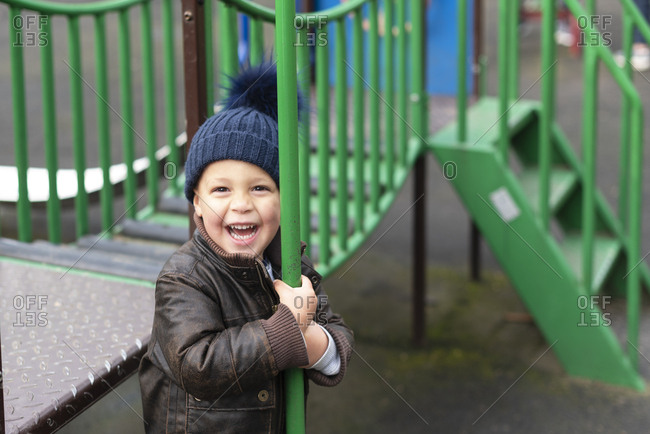 Happy young boy in playground holds fireman's pole