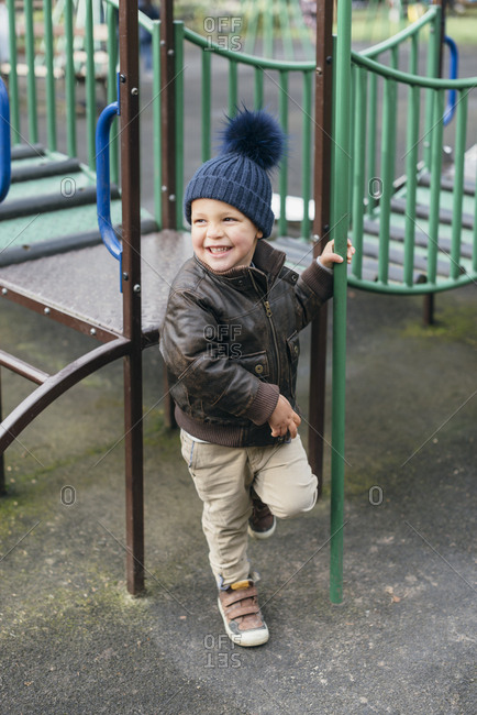Happy young boy holds fireman's pole in playground