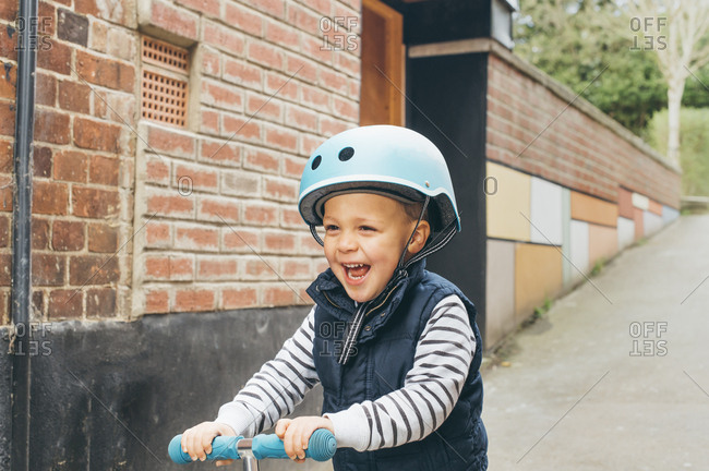 Happy toddler boy riding scooter in street