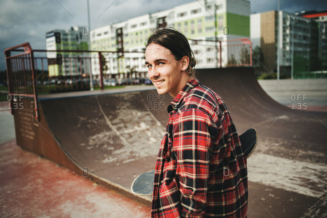 Cheerful teenager with skateboard smiling at camera near ramp in city skate park