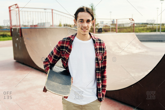 Portrait of handsome teenager with skateboard under arm and hand in pocket looking at camera near ramp in city skate park