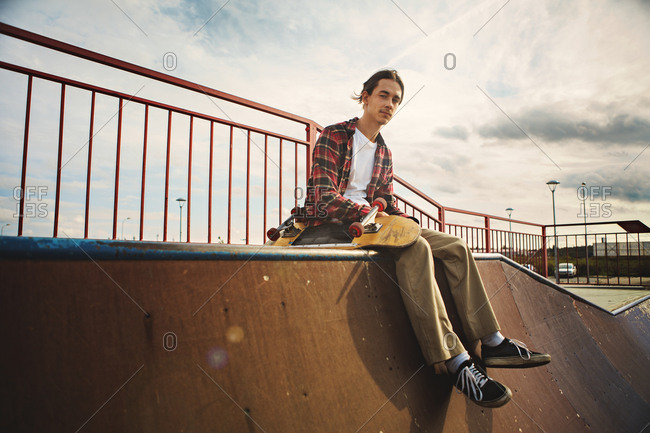 Young man with skateboard looking at camera while sitting on edge of skate park ramp under cloudy sky