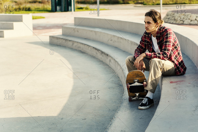 Side view of thoughtful young male in checkered shirt looking away while sitting with skateboard on stairs