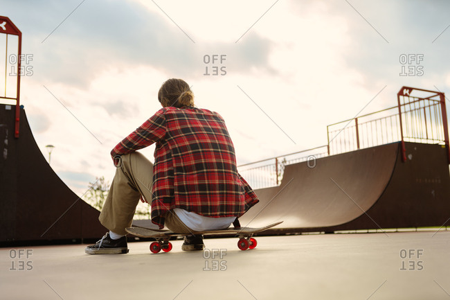 Back view of young rider in checkered shirt sitting on skateboard near ramp in skate park and resting after practice