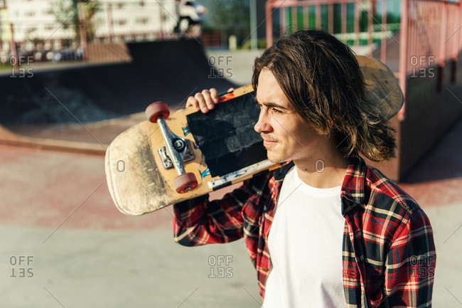 Portrait of handsome young man with long hair looking away while carrying skateboard on his shoulder in skate park