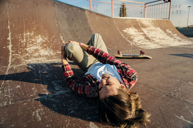 Young skateboarder lying on back in skatepark ramp after painful fall  and holding his injured leg