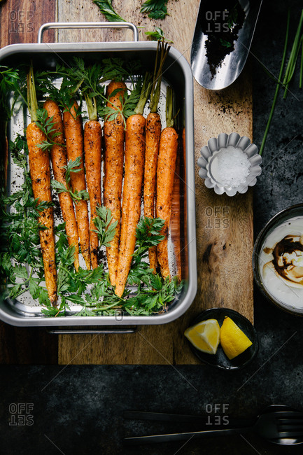 Roasted carrots in a pan beside fresh coffee