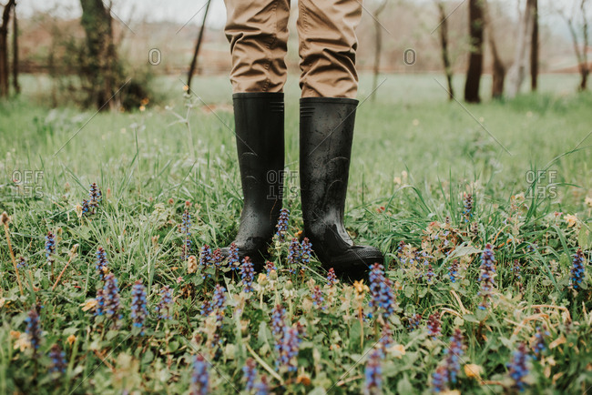 Person wearing rain boots standing in a rural field with wildflowers