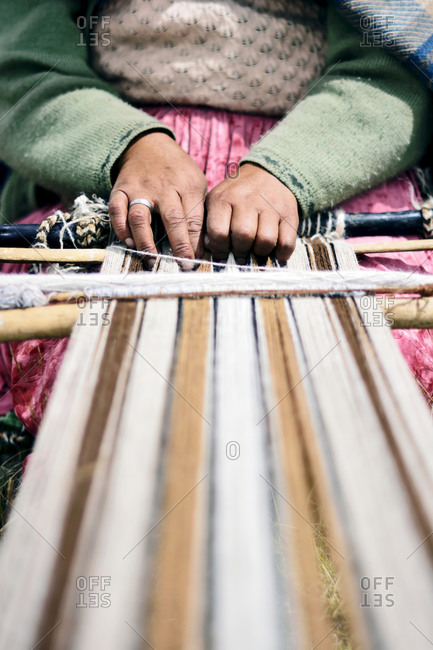 Hands of an Aymara artisan woman weaving with wool