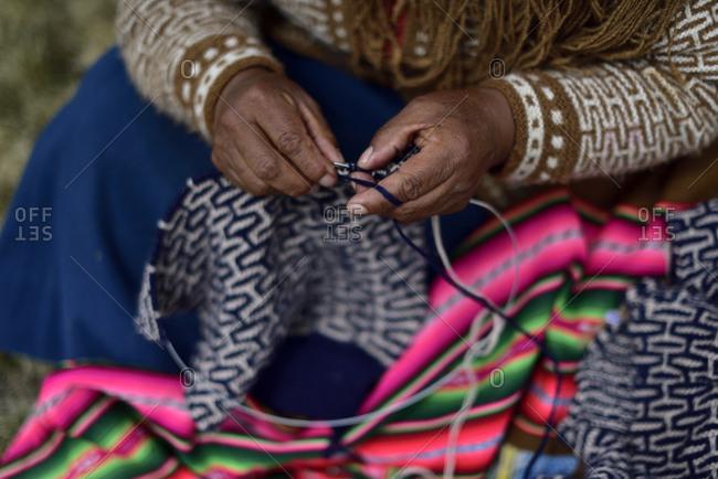 Quechua woman knitting an alpaca coat