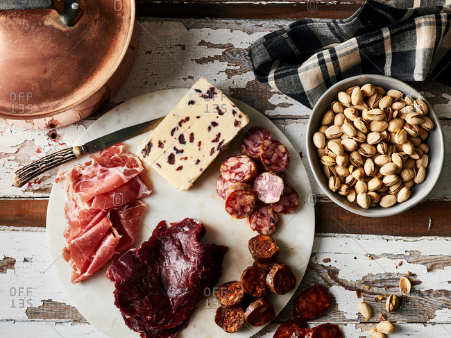 Overhead view of fresh meat and cheese on a charcuterie board