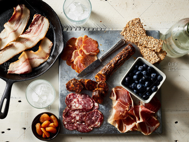 Overhead view of fresh meat on a charcuterie board and bacon in a skillet