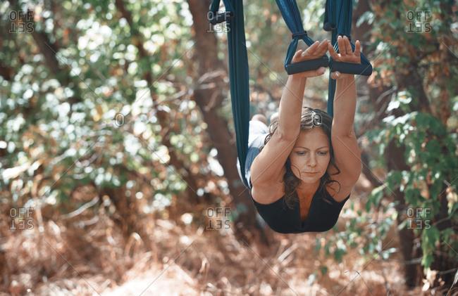 Woman practicing aerial yoga on a hammock