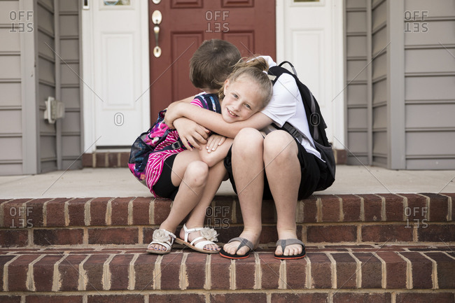 Tween Brother Hugging Blonde Little Sister on Front Steps