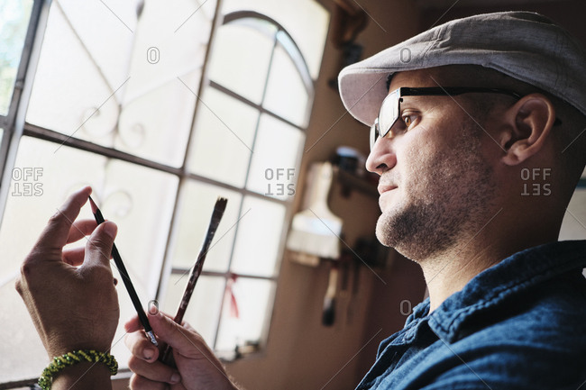 Man working as painter checking brush and pencil tip before painting