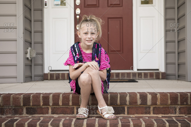 Cute Blonde Curly Headed Girl Waits For School Bus on Front Steps