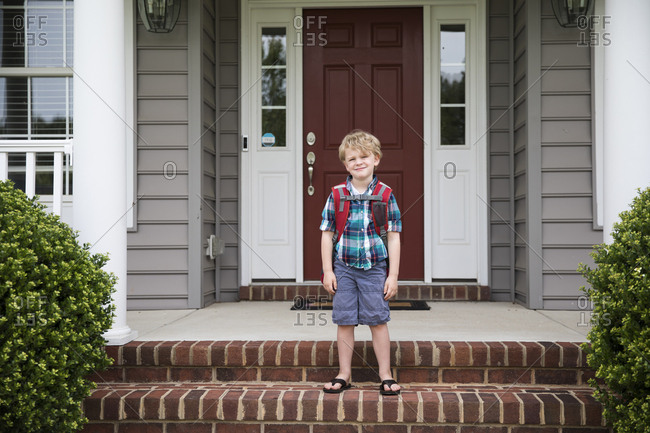 Cute Blonde Curly Headed Boy Waits For School Bus on Front Steps
