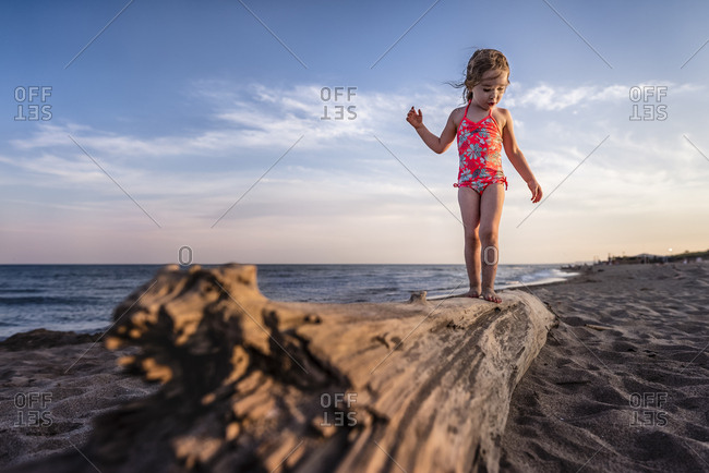 Girl balancing on drift wood log at the beach looks down