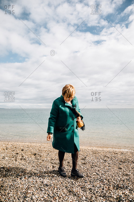 Front view of an senior woman walking by the sea