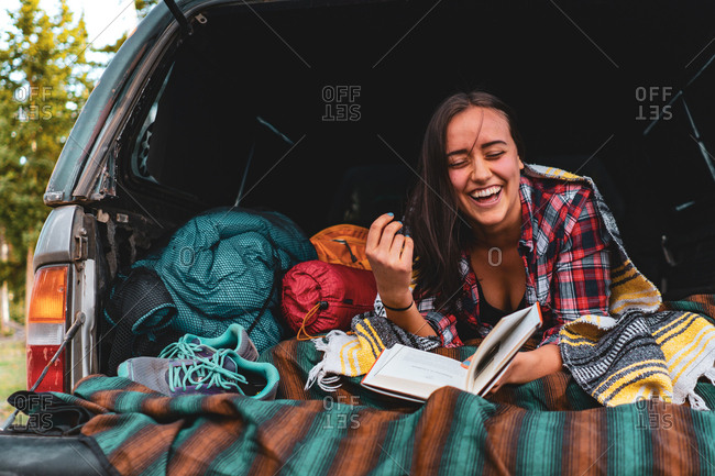 Camp Vibes - Young Woman Laughing while car camping.