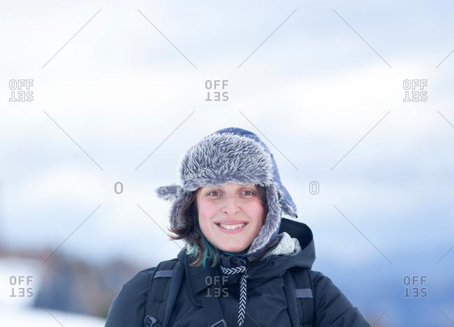 happy woman wearing fur hat in winter