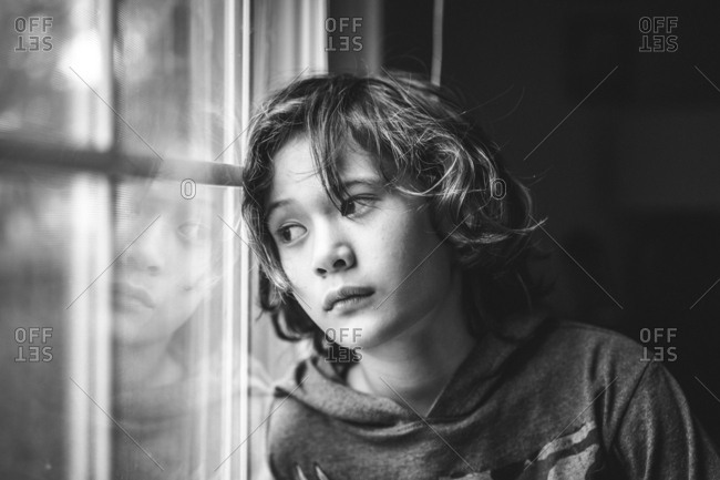 portrait of a young boy gazing out a window with a serious expression
