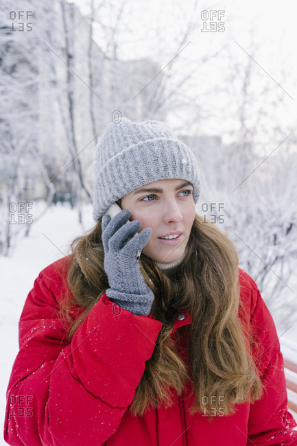 beautiful young woman laughing in red down jacket speaks by phone