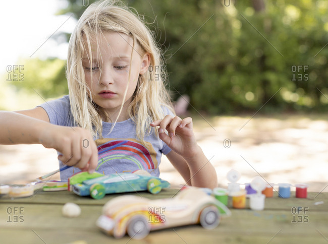 Girl painting a race car  with messy hair