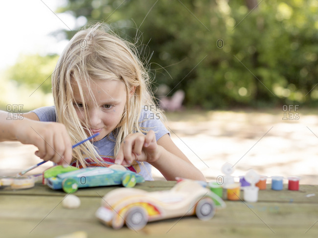 young girl building a toy car