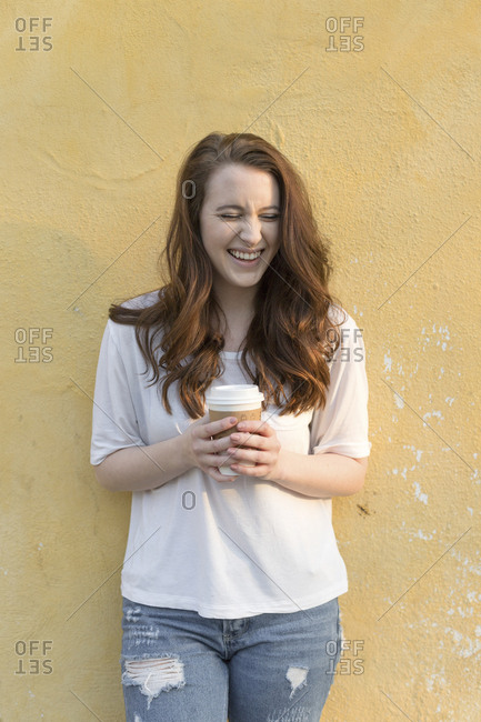 girl laughing with long brown hair holding coffe