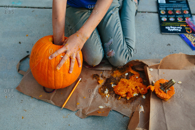 Girl reaches into pumpkin to remove insides with other hand messy