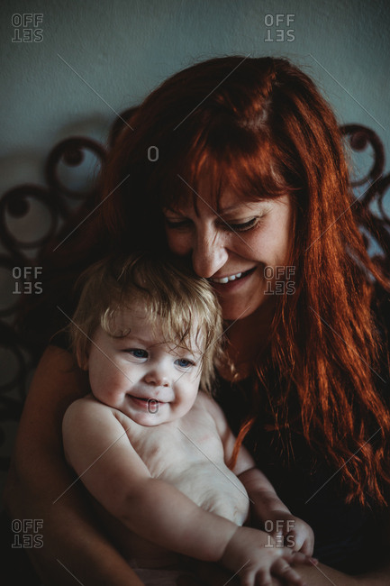 A mother holding a baby with joy and laughter in home on pretty chair