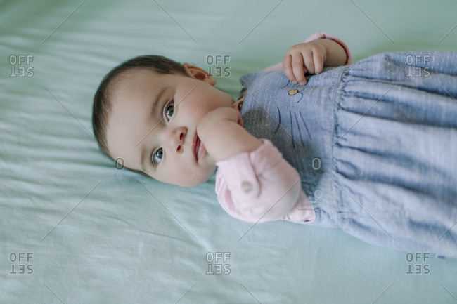 Portrait of cute baby girls lying on bed with fingers in mouth