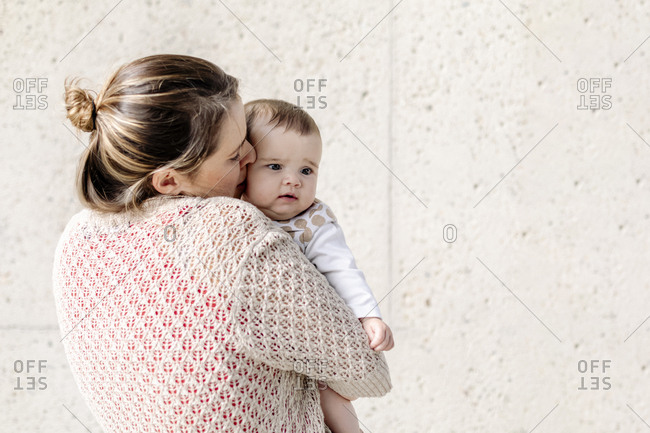 Mom holding and kissing baby who is waking up against concrete wall
