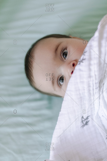 Close up of baby looking up and covered by blanket