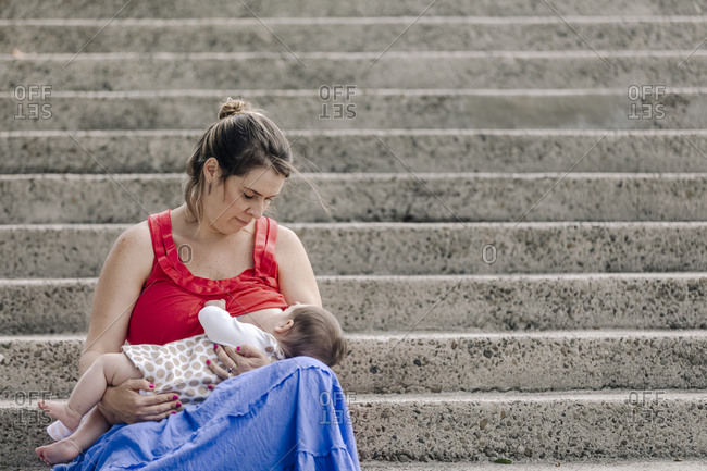 Breastfeeding baby outdoor by staircase