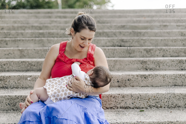 Mom breastfeeding baby girl outdoor in stair
