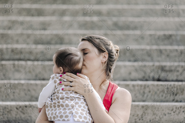 Mother hugging baby girl while sitting on stair outdoor