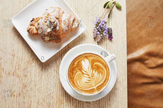 Overhead view of Rosetta cappuccino served with croissant and lavender
