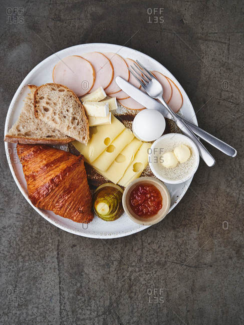 Overhead view of a continental breakfast with croissant, ham, cheese, egg, jam and fruit